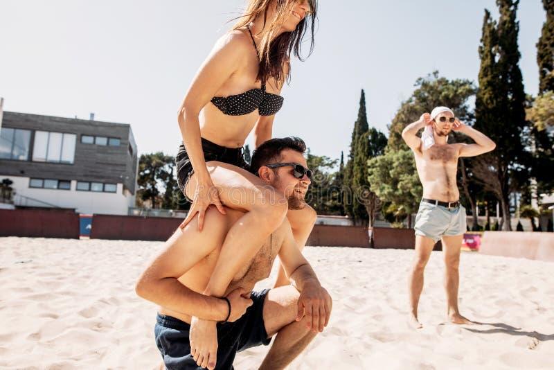 Giovane bello che dà sulle spalle giro alla sua amica sulla spiaggia di estate fotografie stock libere da diritti