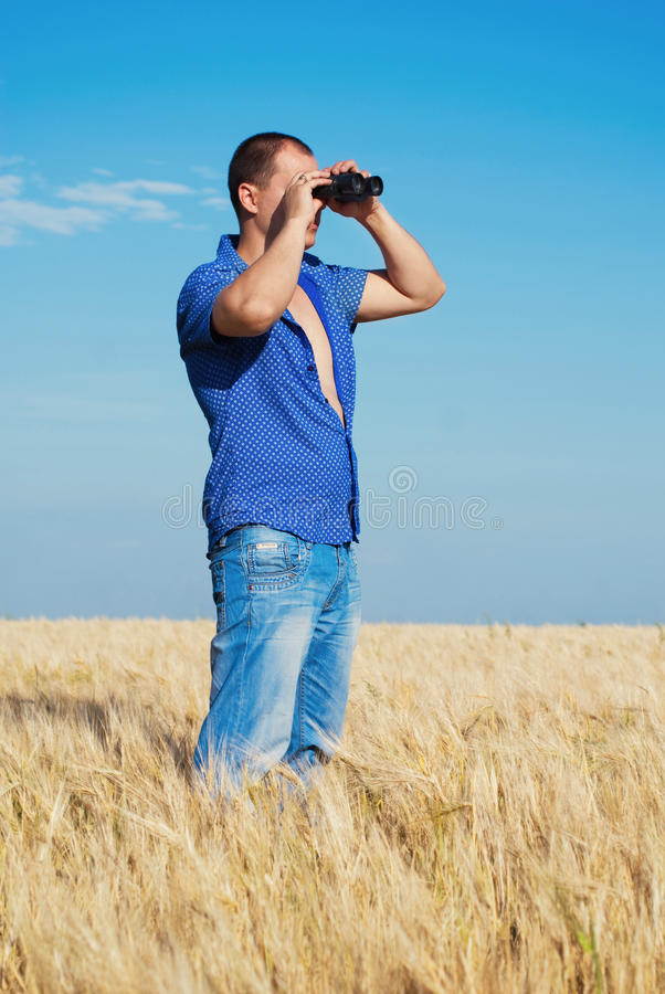 Giovane bello che guarda tramite il binocolo fotografia stock libera da diritti