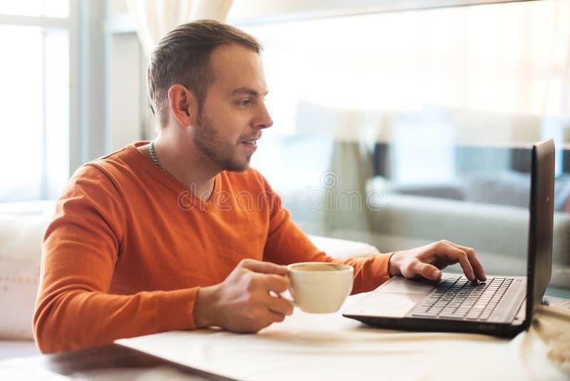 Giovane bello che lavora al taccuino, pensante, mentre godendo del caffè in caffè fotografia stock