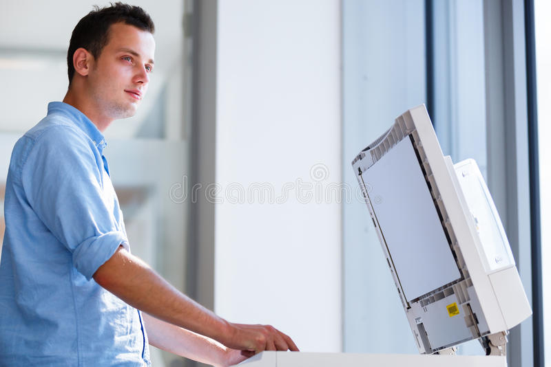 Giovane bello che per mezzo di una macchina della copia immagini stock