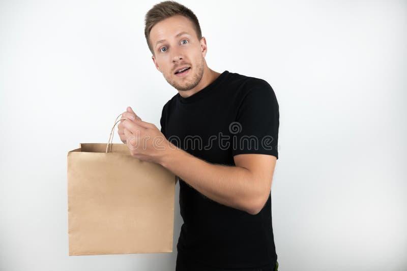 Giovane bello che porta maglietta nera che tiene la borsa di compera del papper del mestiere con le merci che ritornano dal super fotografie stock libere da diritti