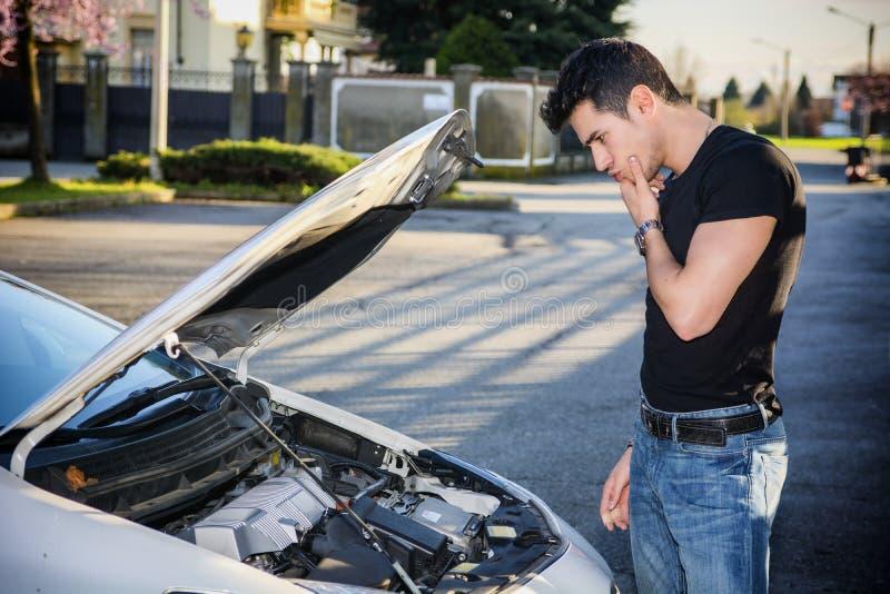 Giovane bello che prova a riparare un motore di automobile immagine stock libera da diritti