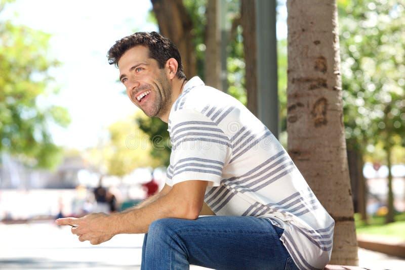 Giovane bello che si siede all'aperto con il telefono cellulare e la risata immagini stock