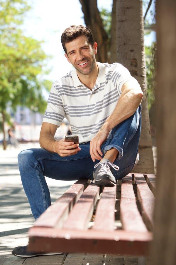 Giovane bello che si siede all'aperto sul banco con il telefono cellulare fotografia stock libera da diritti