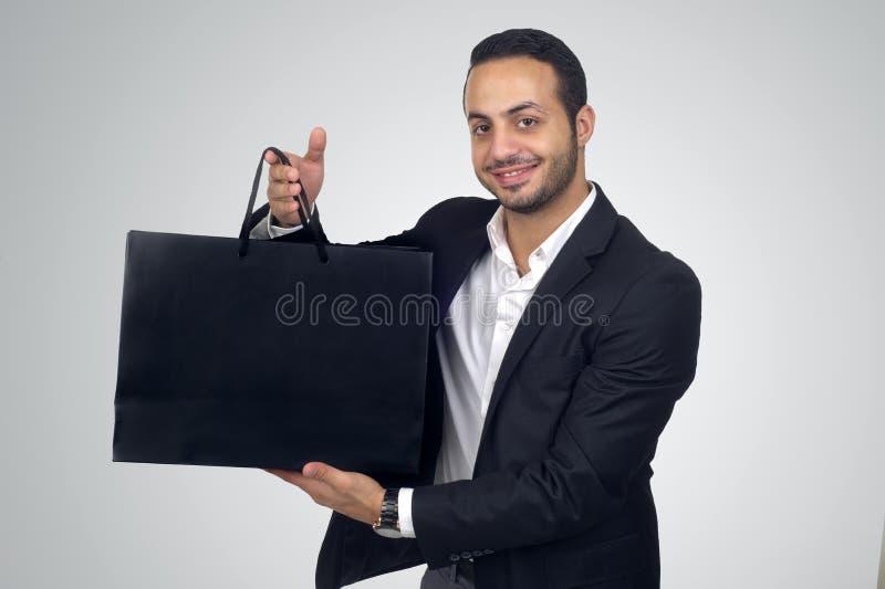 Giovane bello che tiene un sacchetto della spesa nero fotografie stock libere da diritti