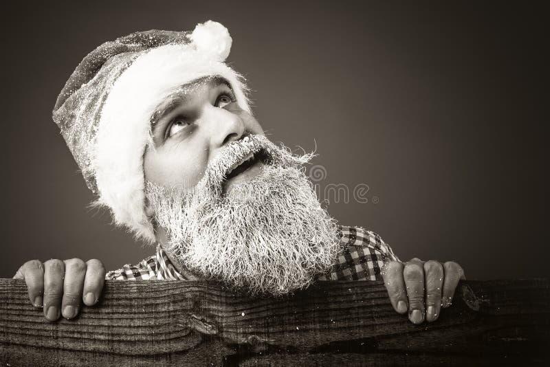 Giovane bello con cercare congelato del cappuccio di Santa e della barba fotografia stock
