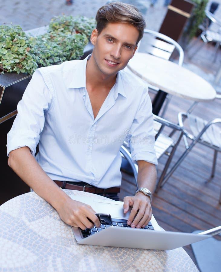 Giovane bello con il computer portatile immagine stock