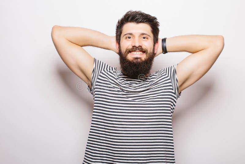 Giovane bello con la barba che si tiene per mano dietro la testa e sorridere immagini stock