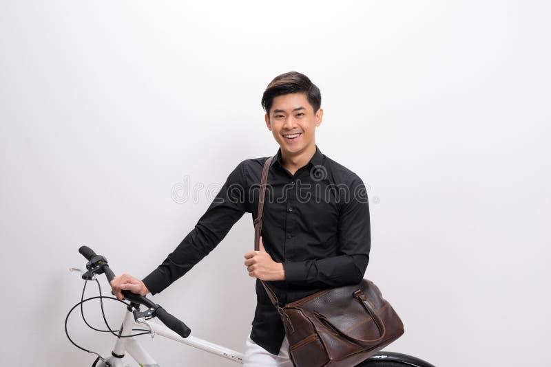 Giovane bello con la condizione della bicicletta e della borsa a tracolla isolato su fondo bianco fotografie stock