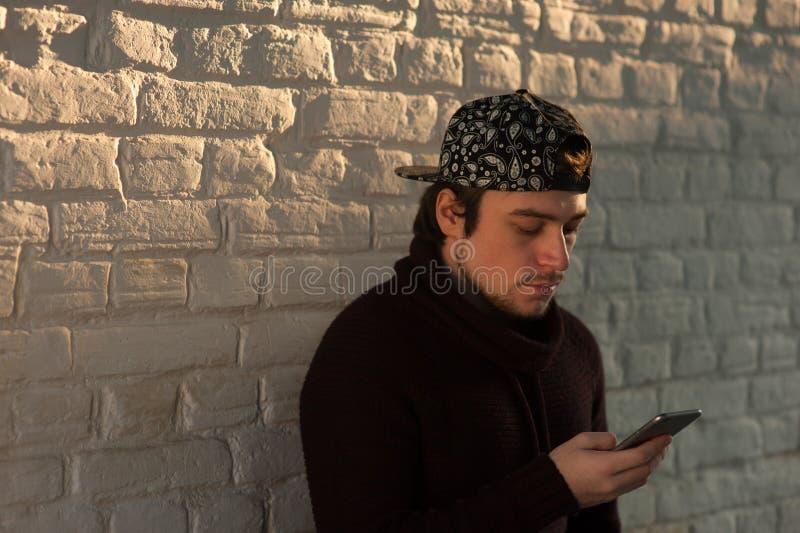 Giovane bello con lo smartphone sul fondo della parete immagini stock