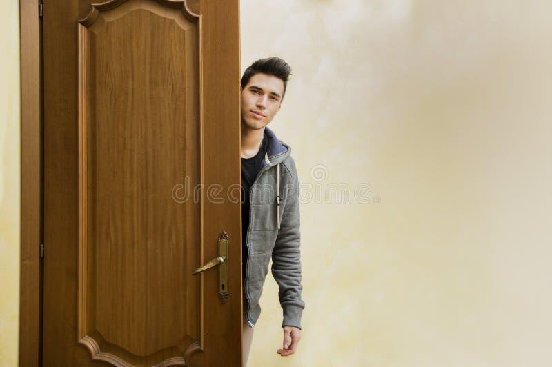 Giovane bello dietro la porta aperta, uscente fotografia stock