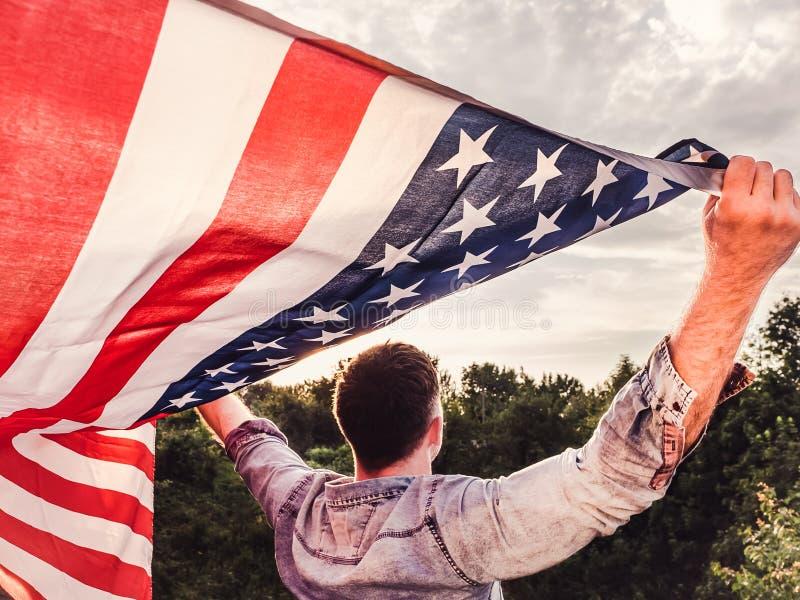 Giovane bello e che tiene una bandiera americana fotografie stock