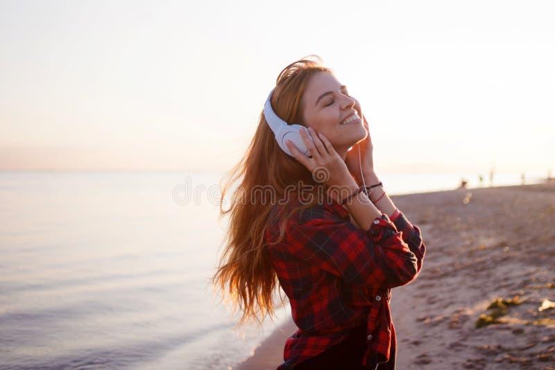 Giovane bello fan della musica femminile Ballando ed ascoltare la musica sulle cuffie immagine stock