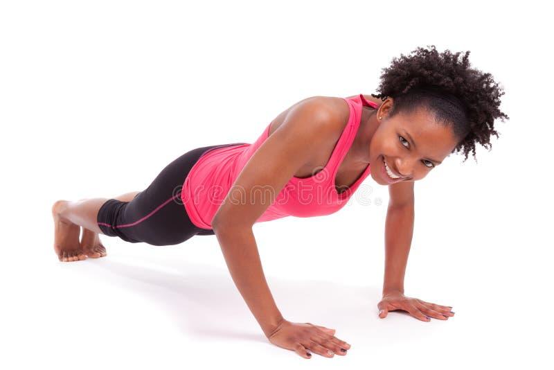 Giovane bello fare africano della donna di forma fisica spinge verso l'alto gli esercizi sopra immagine stock
