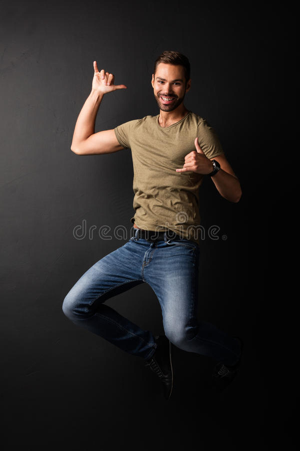 Giovane bello felice che salta e che balla fotografie stock