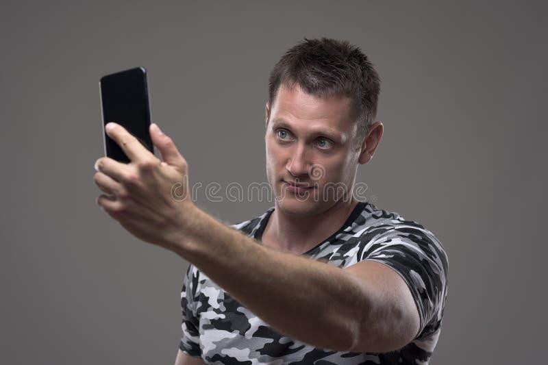 Giovane bello in maglietta del modello del cammuffamento che prende le foto con il telefono cellulare fotografia stock libera da diritti