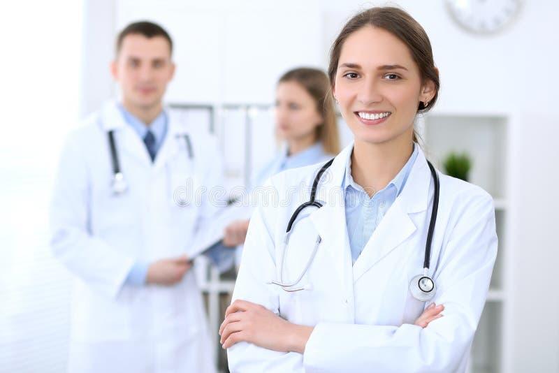 Giovane bello medico femminile che sorride sui precedenti con il paziente in ospedale fotografia stock