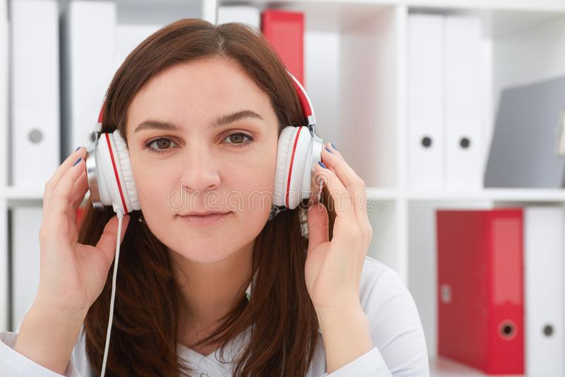 Giovane bello medico femminile della medicina che gode della musica nel suo luogo di lavoro Medico rilassi il concetto fotografia stock libera da diritti
