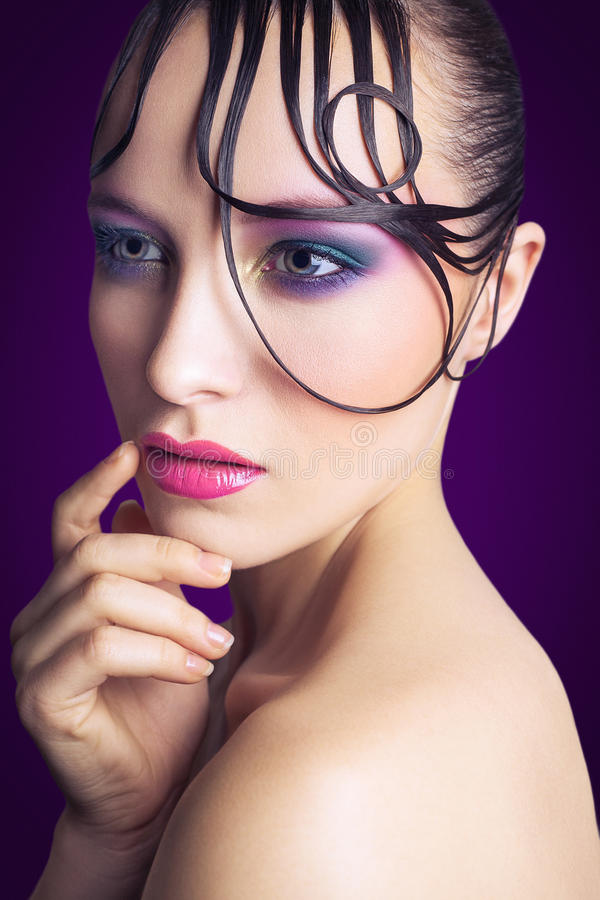 Giovane bello modello di moda con trucco rosa e blu e acconciatura sul suo fronte immagini stock