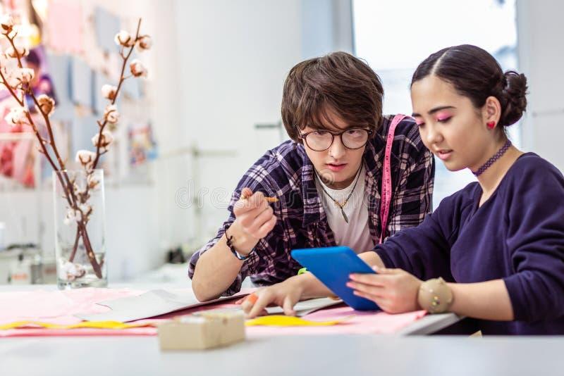 Giovane bello progettista asiatico femminile che guarda il video con il suo collega immagine stock libera da diritti
