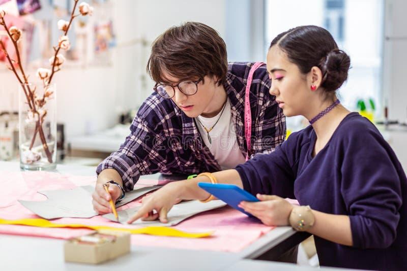 Giovane bello progettista asiatico femminile che tiene una compressa in sue mani immagine stock libera da diritti