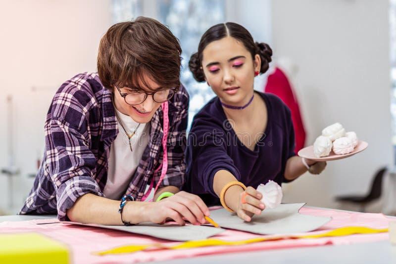 Giovane bello progettista asiatico femminile e suo il collega che hanno rottura sul lavoro immagini stock libere da diritti
