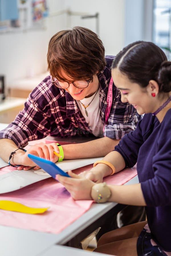 Giovane bello progettista asiatico femminile e suo il collega che sembrano contenti fotografia stock