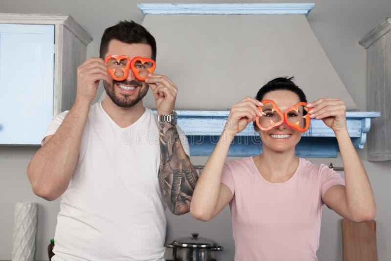 Giovane bello sciocco delle coppie nella cucina Tengono i pezzi di pepe bulgaro intorno ai loro occhi e risata fotografie stock