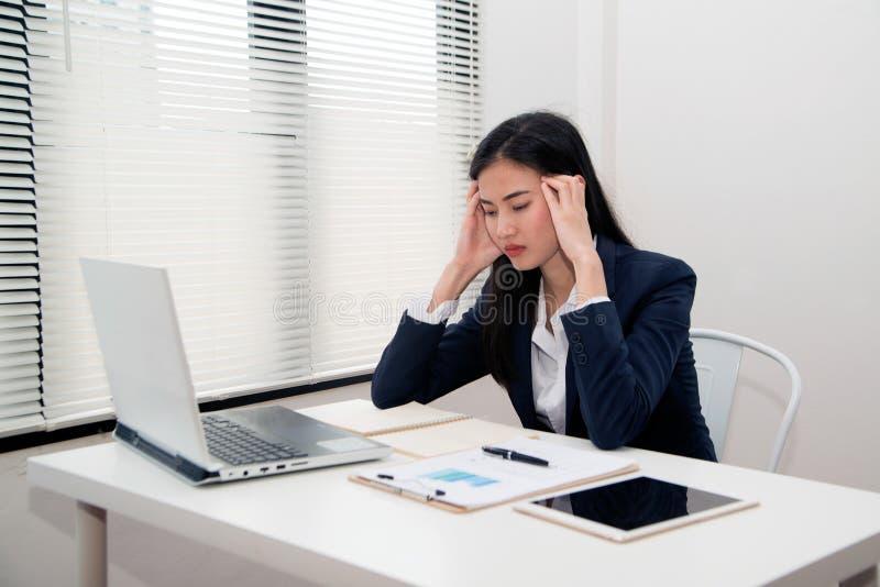 Giovane bello sforzo di sofferenza asiatico della donna di affari che lavora all'ufficio immagini stock libere da diritti