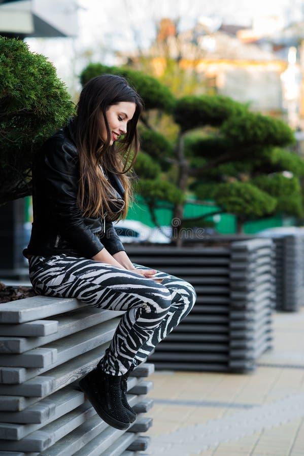 Giovane bello telefono cellulare della tenuta della donna a disposizione e seduta sul banco nel parco della città immagine stock libera da diritti