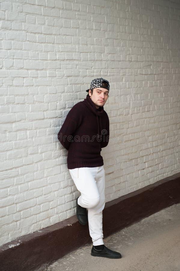 Giovane bello in un berretto da baseball e nei pantaloni bianchi e del maglione fotografia stock libera da diritti