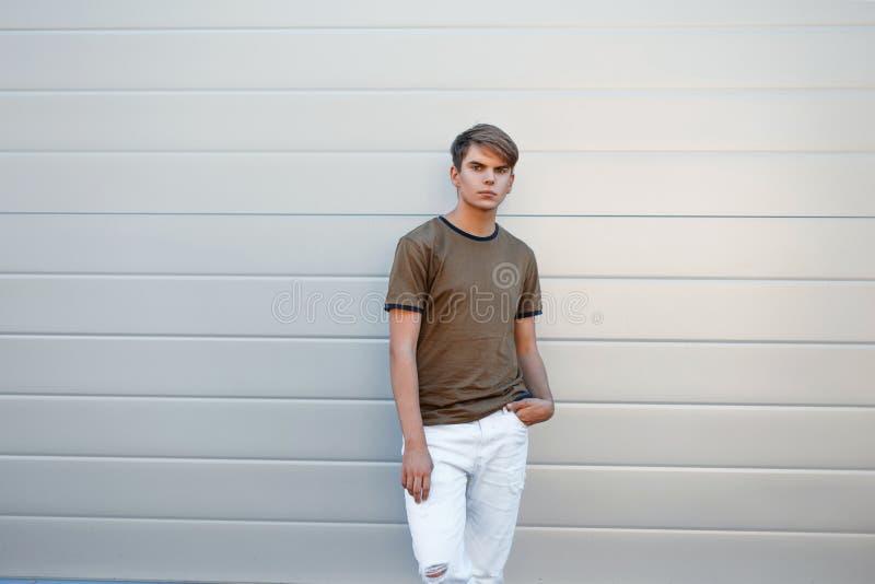 Giovane bello in una maglietta classica di modo e nei pantaloni bianchi fotografia stock libera da diritti