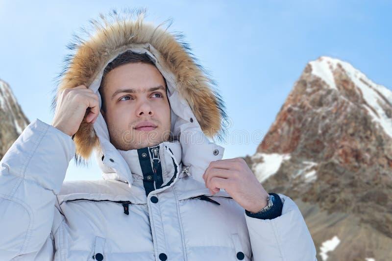 Giovane bello uomo in un rivestimento bianco con il cappuccio della pelliccia in montagne di inverno Ritratto di modo fotografia stock libera da diritti
