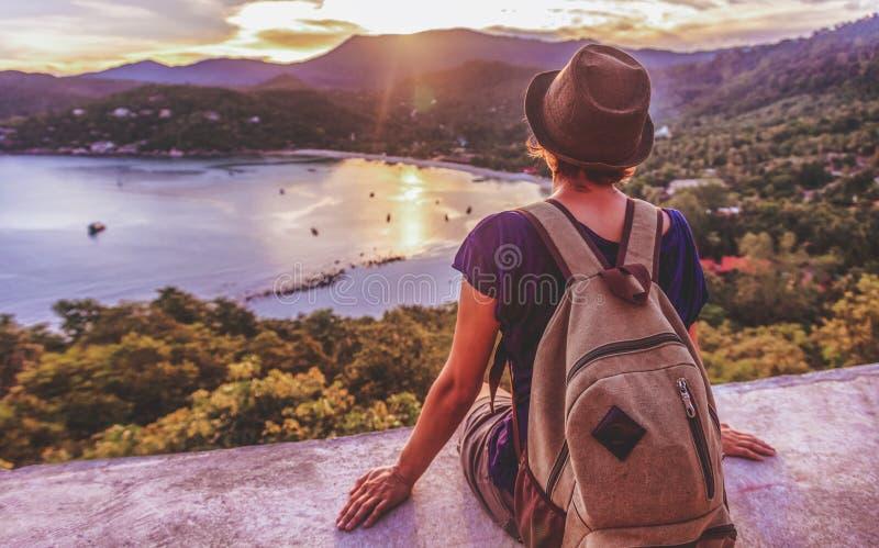 Giovane bello viaggiatore dei pantaloni a vita bassa della donna che esamina tramonto e bea immagini stock