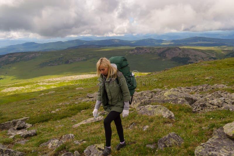 Giovane bello viaggio della donna con il grandi zaino e bottiglia verdi, fotografie stock