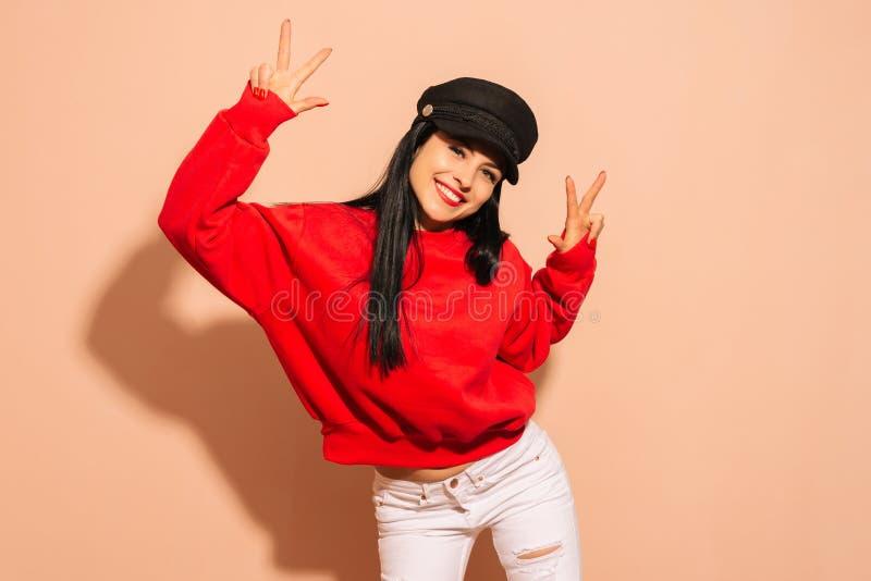 Giovane berretto nero d'uso sorridente della ragazza e maglia con cappuccio rossa sopra fondo isolato che guarda alla macchina fo immagine stock libera da diritti