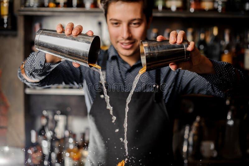 Giovane bevanda di versamento sorridente del barista con le fette di frutta arancio fresca fotografia stock
