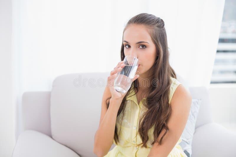 Giovane bicchiere d'acqua di tenuta castana calmo immagine stock