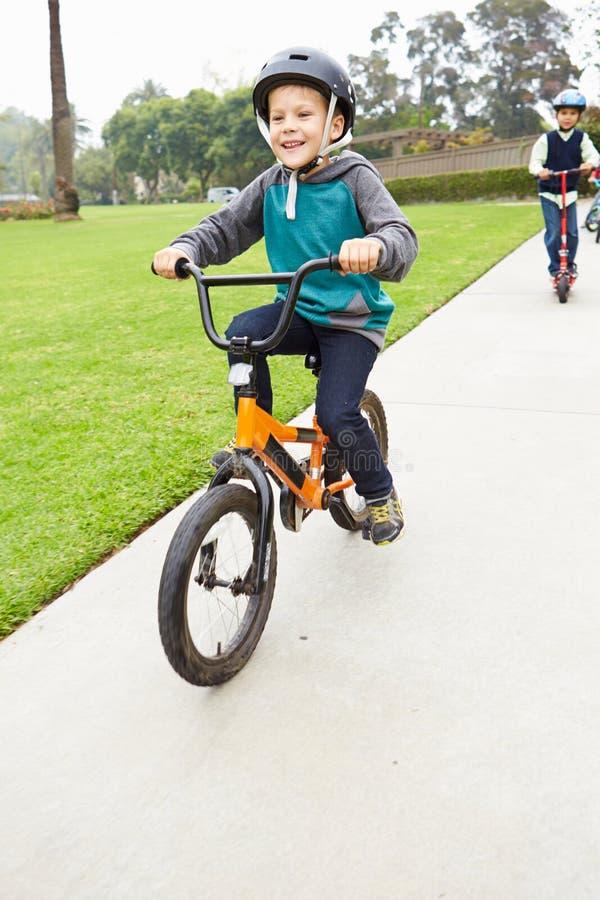 Giovane bici di guida del ragazzo in parco fotografie stock libere da diritti