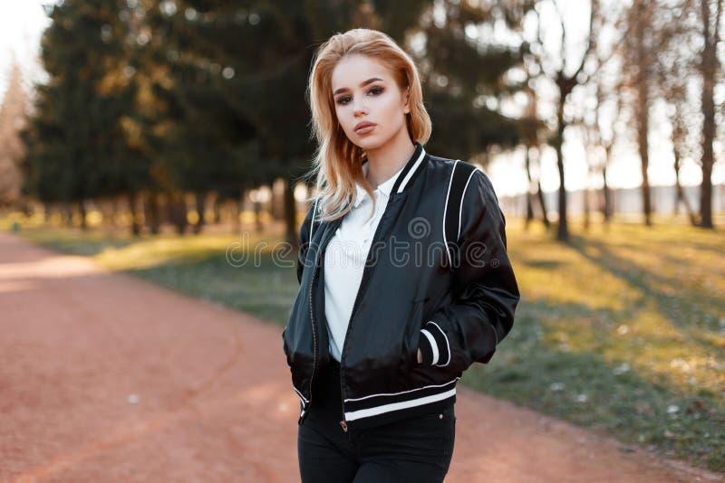 Giovane bionda affascinante della donna con i bei occhi in una camicia bianca alla moda in un rivestimento nero leggero alla moda immagine stock libera da diritti