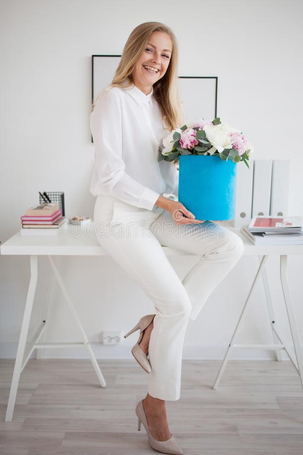 Giovane bionda alla moda in ufficio, camicia bianca e pantaloni Tiene un mazzo lussuoso delle peonie in un contenitore blu di cap fotografia stock