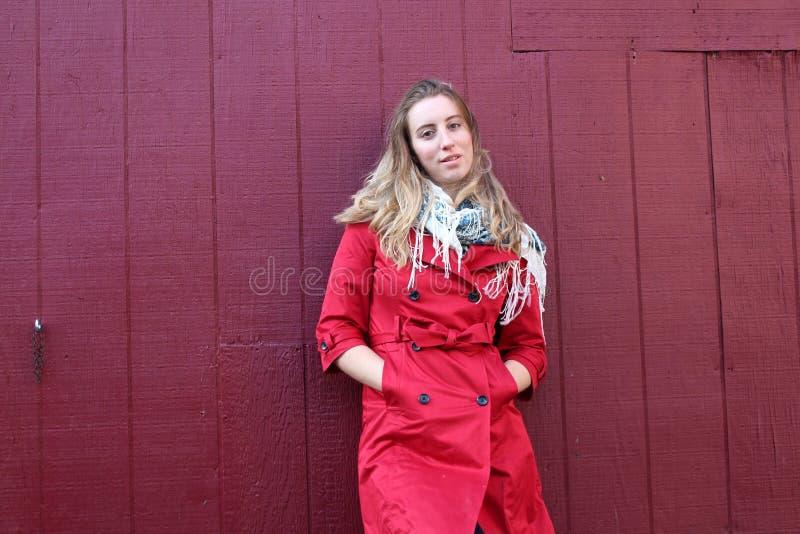 Giovane bionda contro la parete rossa fotografie stock
