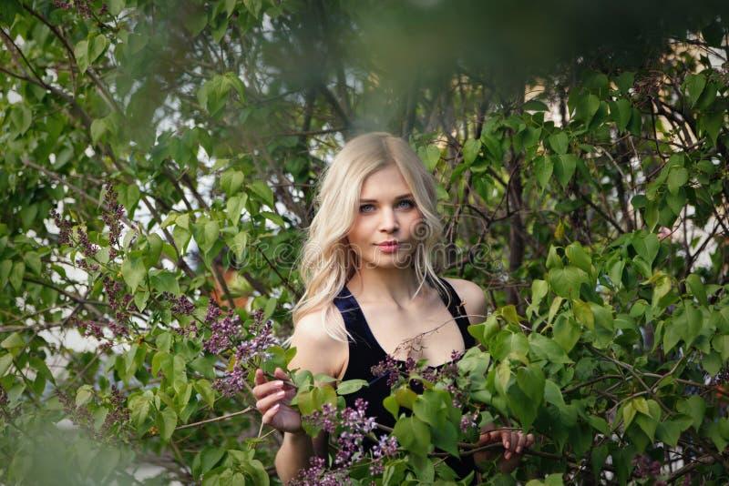 Giovane bionda dalla carnagione chiara favorita impertinente sexy che posa accanto a Bush del lillà di fioritura Fuoco molle, spa immagini stock libere da diritti