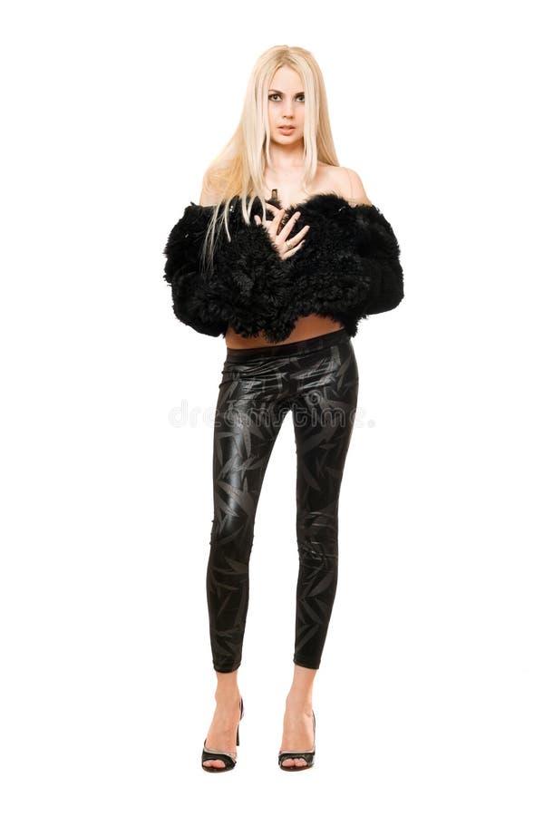 Giovane bionda piacevole in cappotto e ghette neri immagini stock