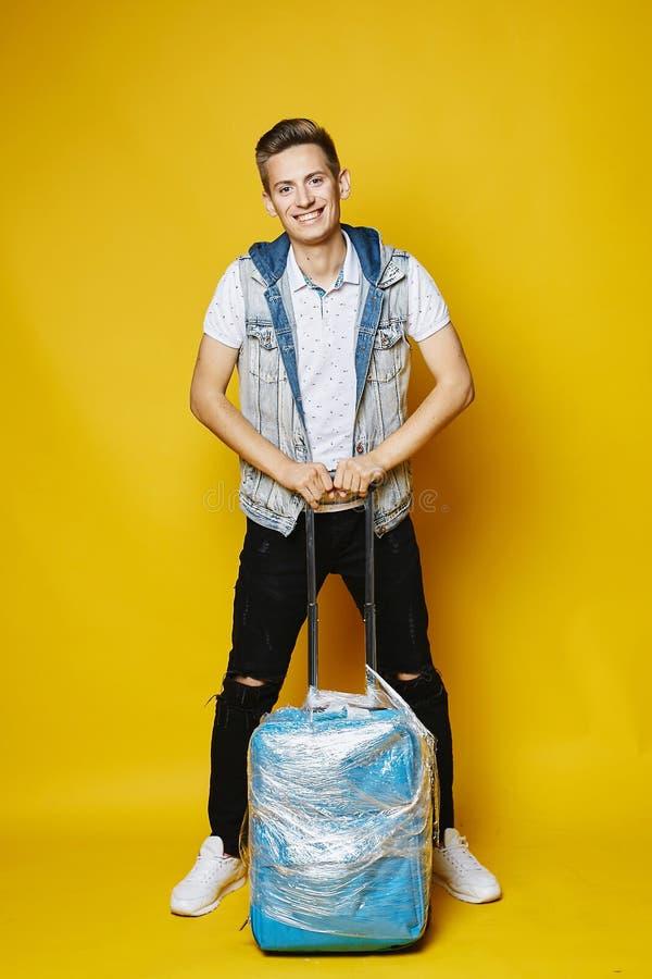 Giovane biondo alla moda in jeans neri e maglietta bianca, isolati in integrale con la valigia blu a fondo giallo fotografia stock libera da diritti