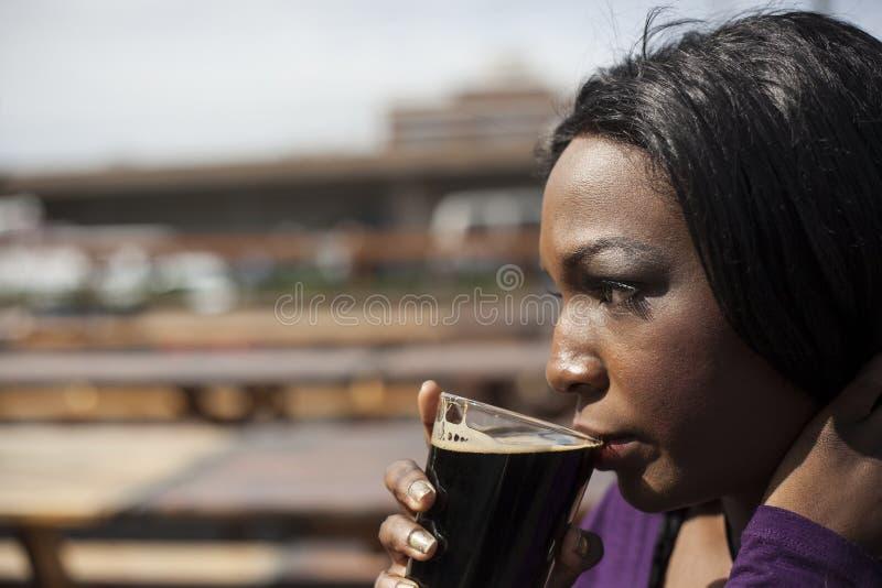 Giovane afroamericano WomanDrinks una birra di malto immagine stock