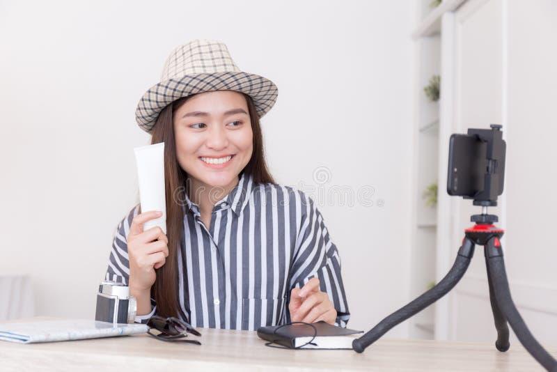 Giovane blogger asiatico di viaggio della donna che tiene protezione solare, video d'istruzione di registrazione per dividere sui immagini stock libere da diritti