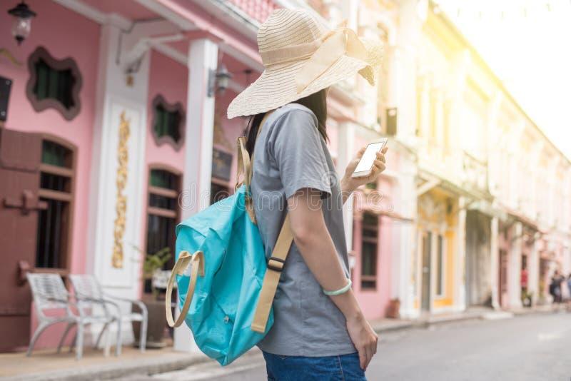 Giovane blogger o viaggiatore con zaino e sacco a pelo di viaggio asiatico facendo uso dell'applicazione dell'itinerario sul tele fotografie stock