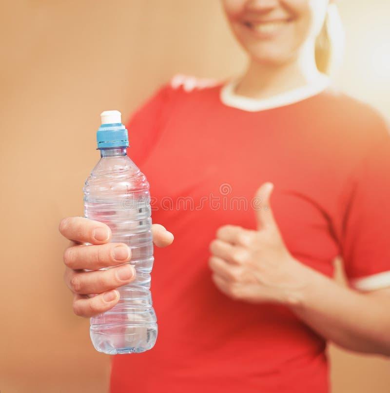Giovane bottiglia della plastica della tenuta della donna dello smilingl Pollici in su focused fotografia stock libera da diritti