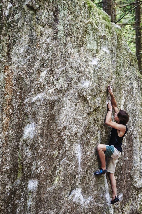 Giovane bouldering del ragazzo all'aperto fotografia stock